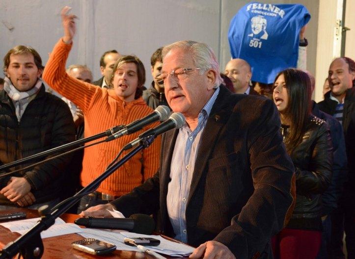 Fellner, habla. Su hijo (de naranja, a la izquierda) agita vítores a favor de su papá.